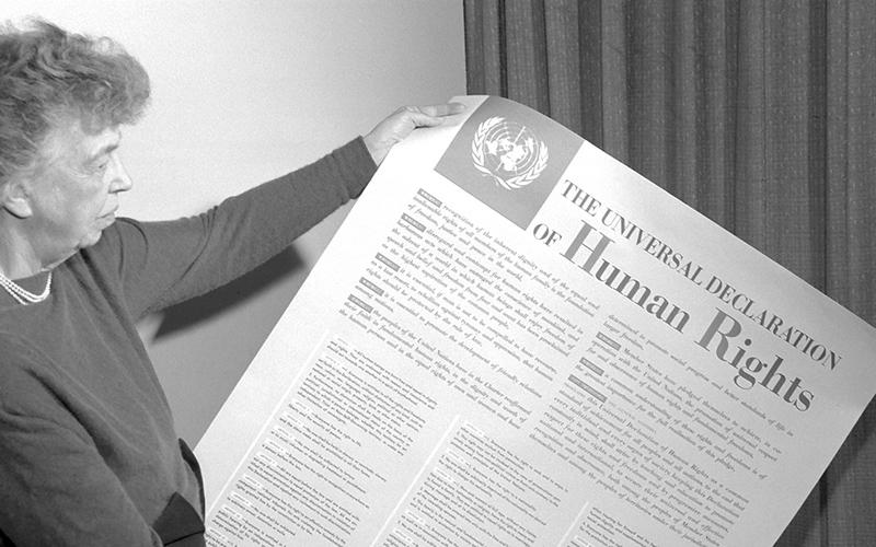 Eleanor Roosevelt holding a copy of the UDHR.